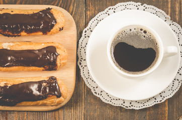 eclairs with chocolate and a coffee cup/eclairs with chocolate and a coffee cup on a wooden background. Top view