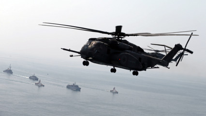 A U.S. Navy MH-53E Sea Dragon helicopter flies over U.S. and U.K. Navy ships during a U.S. and U.K. Mine Countermeasures Exercise (MCMEX) taking place at the Arabian Sea