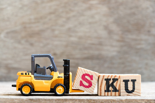 Toy forklift hold letter block S in word SKU (abbreviation of stock keeping unit) on wood background