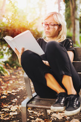 Young adult blonde girl reading a book outdoor in a park chair. Blank white book cover