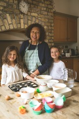 Grandmother standing with her granddaughters in kitchen