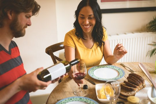 Man serving red wine to woman