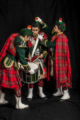 Two pipers and snare drummer of an Indian American Scottish bagpipe band in full Scottish regalia, including kilts and sporrans getting ready for a performance