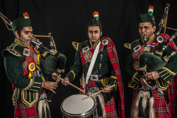 Two pipers and snare drummer of an Indian American Scottish bagpipe band in full Scottish regalia, including kilts and sporrans