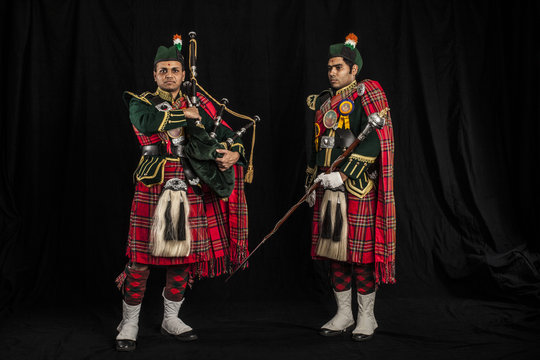 Drum major and piper of an Indian American Scottish bagpipe looking at camera in full Scottish regalia, including kilts and sporrans