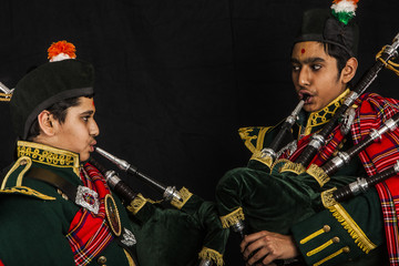 Two pipers of an Indian American Scottish bagpipe playing bagpipes looking away from camera in full Scottish regalia, including kilts and sporrans