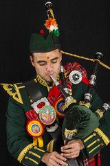 A portrait of an Indian American Scottish bagpiper playing the bagpipe and looking away camera in full Scottish regalia, including kilt and sporrans
