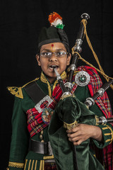 A portrait of an Indian American Scottish bagpiper looking at camera in full Scottish regalia, including kilt and sporrans