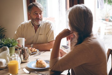 Senior couple interacting with each other while having breakfast