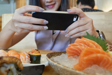 Asian woman taking photo on japanese food in restaurant by smart phone