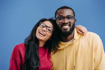 portrait of happy african american couple in eyeglasses looking at camera isolated on blue background