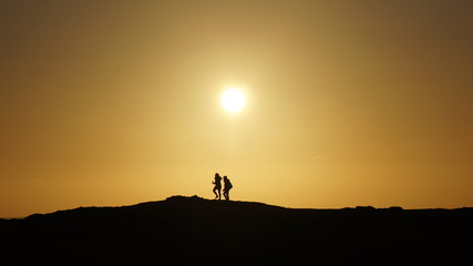 Silhouette Couple Walking against an Golden Sunset