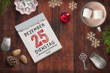 weihnachtliche Dekoration und Abreißkalender mit dem 25.12.2018 auf rustikalem Holzuntergrund