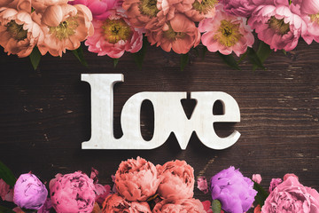 """word """"love"""" on wooden background with many flowers"""