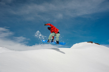 29da35f60ef4 guy is jumping on a snowboard against a blue sky and snow-capped ...