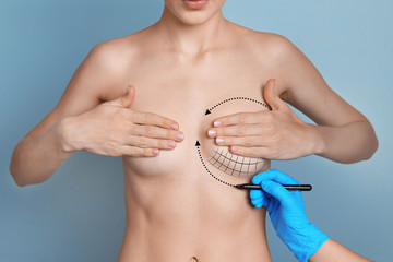 Doctor marking woman breast on color background. Cosmetic surgery