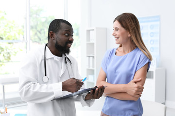 Young African-American doctor consulting patient in modern hospital