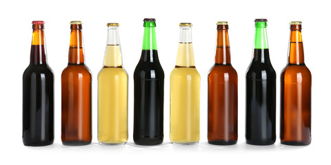 Bottles with different beer on white background