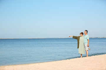 Happy mature couple walking at beach on sunny day