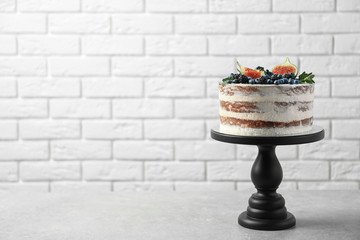Delicious homemade cake with fresh berries on table against brick wall. Space for text