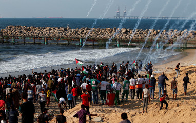 Tear gas canisters are fired by Israeli troops towards Palestinian demonstrators during a protest calling for lifting the Israeli blockade on Gaza, on a beach near the maritime border with Israel, in the northern Gaza Strip