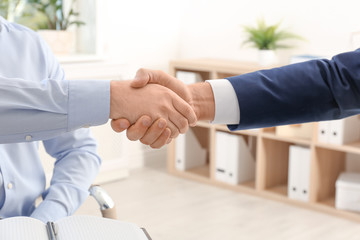 Lawyer handshaking with client in office, closeup