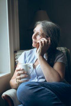 Senior woman talking on mobile phone while having coffee