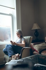 Senior woman using mobile phone in living room