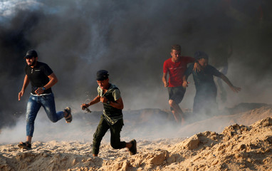 Palestinians run for cover from tear gas fired by Israeli troops during a protest calling for lifting the Israeli blockade on Gaza, on a beach near the maritime border with Israel, in the northern Gaza Strip