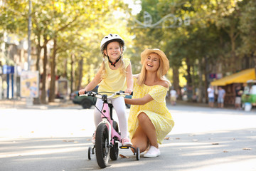 Mother teaching daughter to ride bicycle on street