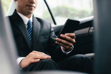 Young business man with phone in car.
