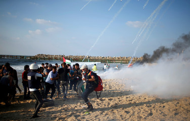 Tear gas canisters are fired by Israeli troops towards Palestinians during a protest calling for lifting the Israeli blockade on Gaza, on a beach near the maritime border with Israel, in the northern Gaza Strip
