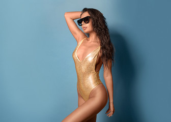 Sexy brunette in a gold swimsuit and sunglasses