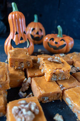 Pumpkin fudge squares with walnuts in cute Halloween setting with smiling pumpkins