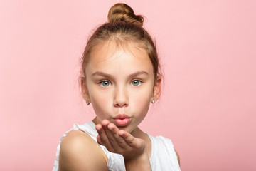 cute little girl blowing a kiss. pretty young child sending love. romance and warm feelings concept. portrait on pink background.