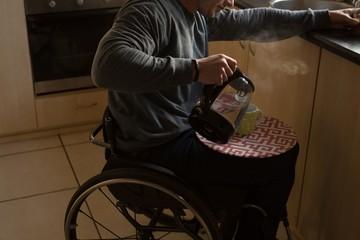 Disabled man preparing coffee in kitchen