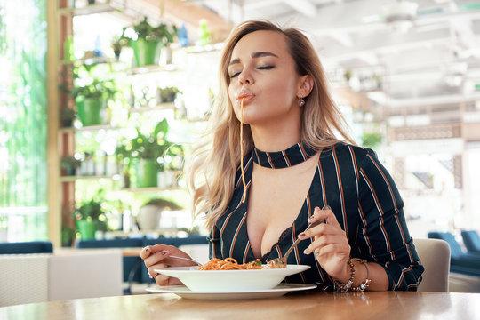 Seductive woman eating pasta