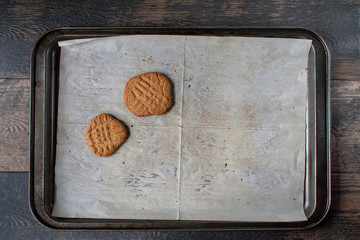 baking tray with white parchment with two Peanut butter cookies