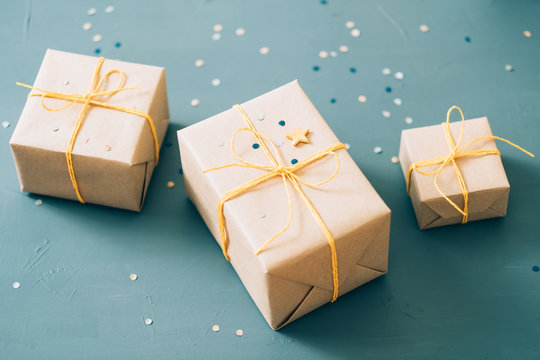 handmade presents. three gift boxes packaged in craft paper and tied with yellow twine on blue background.