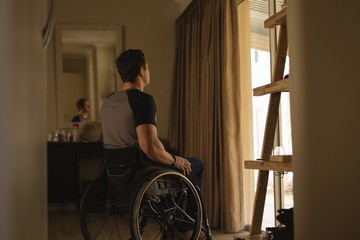 Disabled man in wheelchair at home