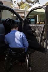 Disabled man in wheelchair near car