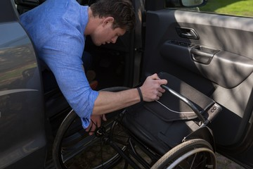 Disabled man holding wheelchair getting in the car