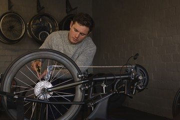 Disabled man repairing wheelchair at workshop