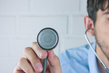 ..Doctor holding up the disc of a stethoscope