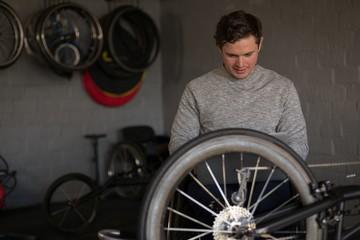 Disabled man repairing wheelchair at workshop