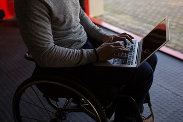 Disabled man using laptop in workshop