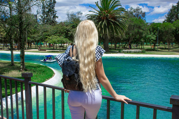 Beautiful young blond woman standing with her back on the bridge and looking at a beautiful landscape, pond and overlooking the park and palm trees.
