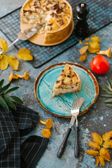 Fresh quiche with wild mushrooms served with autumn leaves on stone background