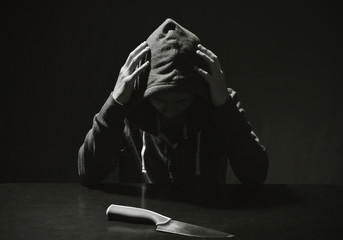 Mysterious man hooded and knife in interrogation room. committed a crime concept.