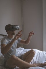 Man using virtual reality headset in bedroom